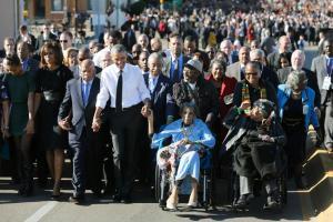 Barack Obama canta acompañado de los manifestantes de la marcha de Selma que cruzaron el puente Edmund Pettus hace 50 años. SAUL LOEB